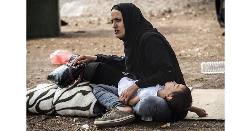 Una donna migrante con il suo bambino, foto SIR.